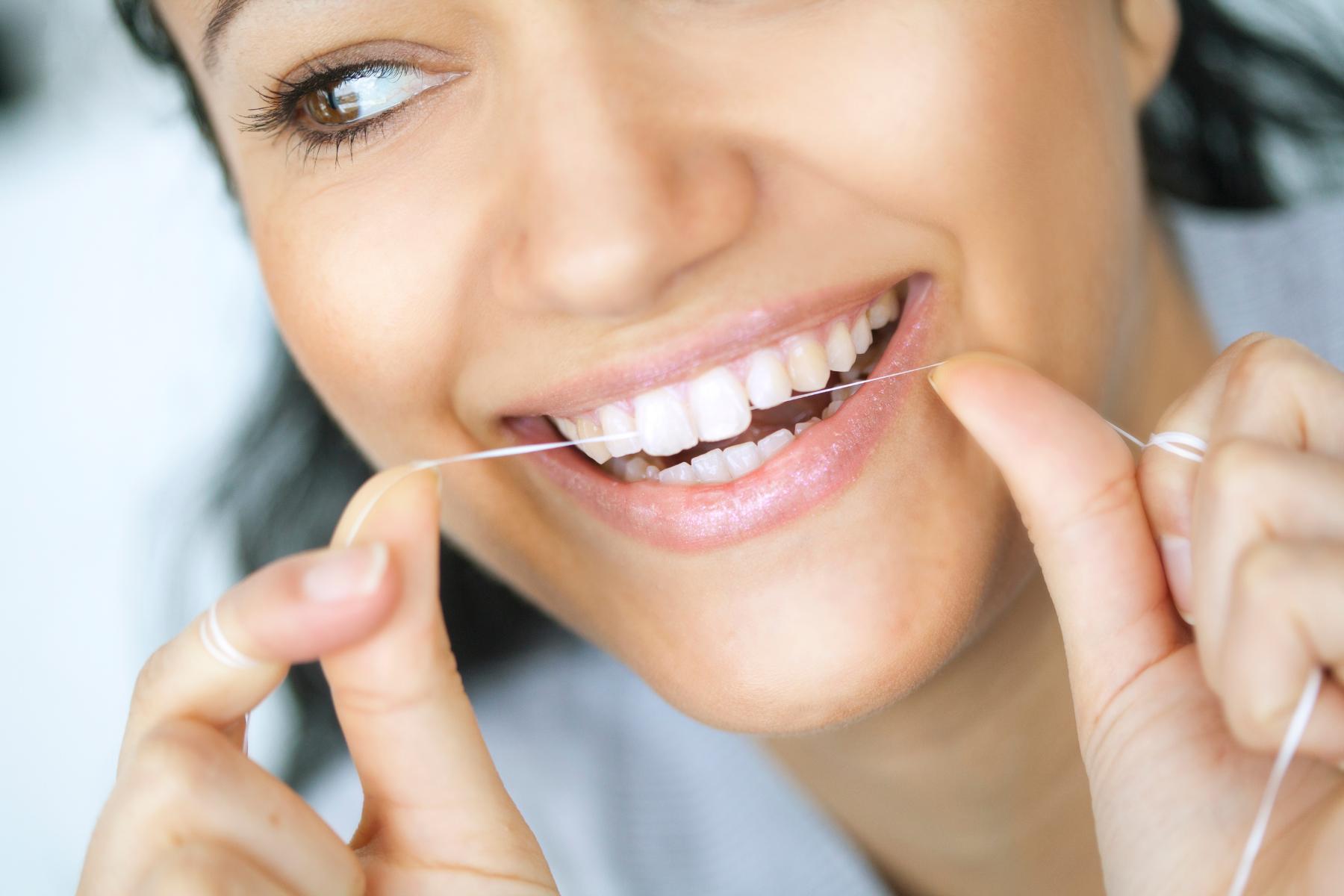 sieviete, kas ar zobu diegu tīra savus zobus